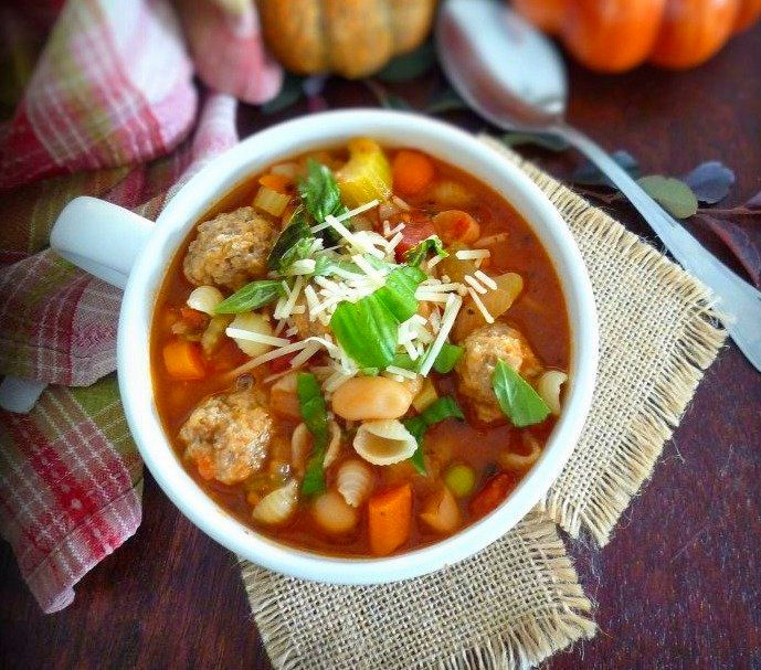 A delicious hearty Italian Sausage and Vegetable Soup guaranteed to soothe your soul and fill your belly with warmth this fall; combining homemade Italian Sausage meatballs, a rich tomato and vegetable soup base with fresh Italian-style vegetables, Italian herbs, and topped with Romano cheese