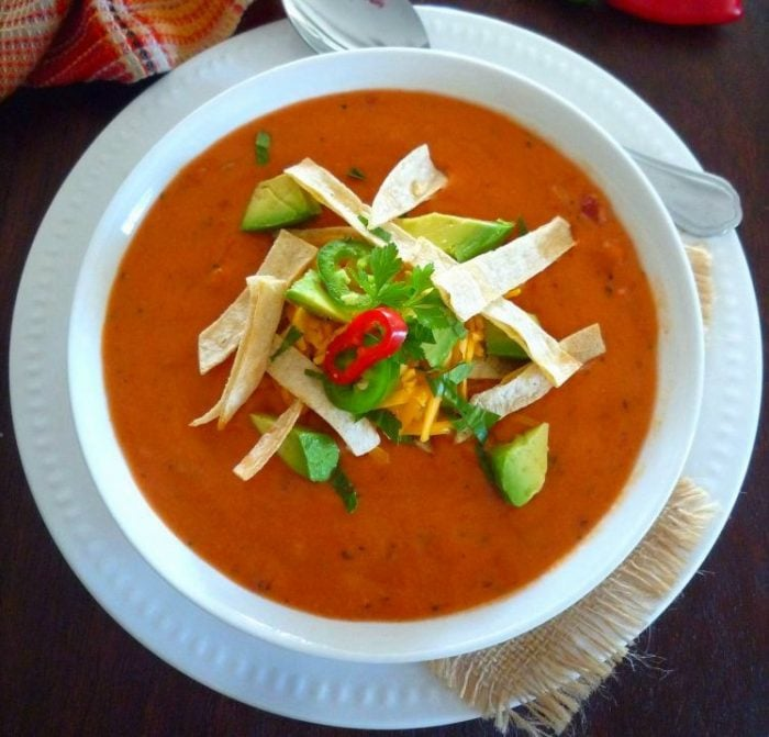 Creamy Homemade Mexican Tomato Soup is hands down the best homemade tomato soup I have ever tasted in my life. Made with organic tomato purée, organic diced tomatoes, roasted red peppers, fresh garlic, onions, chili peppers, fresh Mexican oregano, cilantro, fresh lime juice, heavy cream, ground cumin,  ground coriander, and ground cayenne pepper topped with tortilla strips, mild cheddar,  ripe avocado,  and jalapeño peppers.