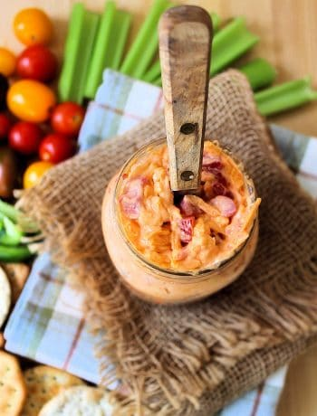 Pimento Cheese, aka Southern Caviar, is one of our favorite delicious iconic Southern Staples. It ranks right up there with our fried okra, cornbread, and collard greens. You'll find us Southerners slathering it on several things, such as celery, soda crackers, Triscuits, grilled cheese, hot dogs, hamburgers, deviled eggs, and even on sweet rolls as little finger sandwiches with a pickle on top.
