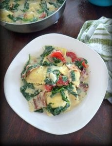 You'll love this simple, easy to make Creamy Ravioli with Bacon Spinach and Red Roasted Peppers , made with quality cheese stuffed Ravioli, fresh organic spinach, Hickory smoked thick sliced bacon, freshly roasted red sweet bell peppers, shallots, all covered in a thick, rich, creamy, homemade four cheese Alfredo sauce.