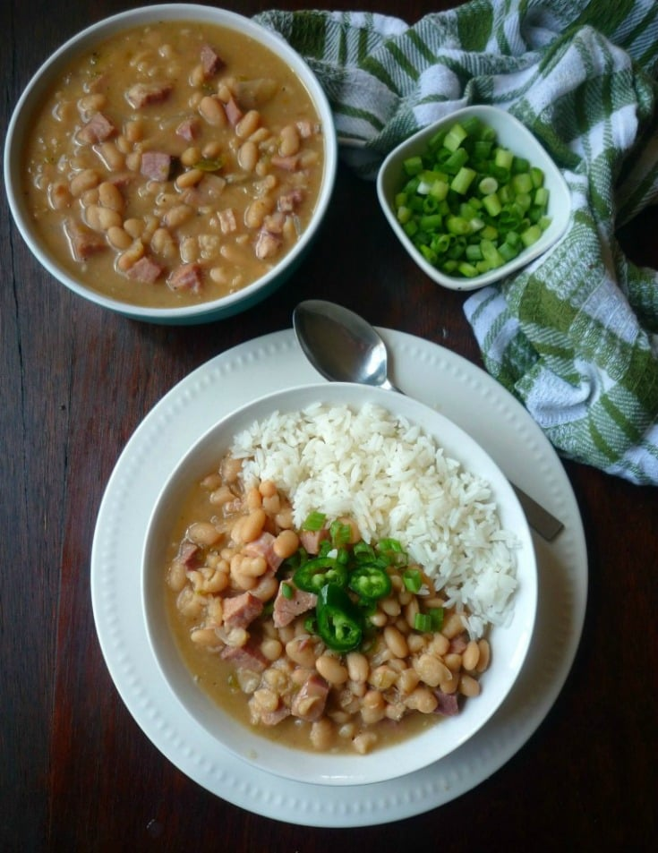 Nothing quite adds a little Southern goodness in your mouth like a big ole pot of slowly simmered Southern-Style White Beans and Ham topped with fresh sliced garden fresh green onions, diced jalapeño peppers, and served with freshly cooked collard greens and a nice warm buttery slice of cornbread.