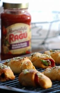 Easy Peasy Pepperoni Pizza Rolls with RAGÚ® Sauce comes together in almost no time at all; made with Crescent rolls, deli sliced sandwich pepperoni, sliced provolone cheese, crisp green bell peppers, and RAGÚ® Homestyle sauce,  baked to perfection in the oven, then brushed with hot garlic butter and served with more delicious RAGÚ® Homestyle sauce for dipping .