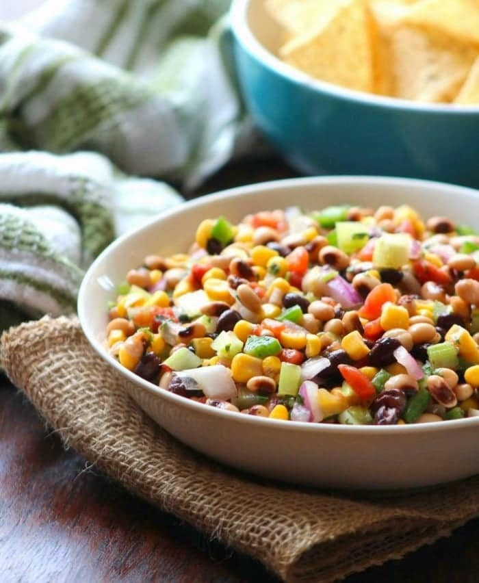 Cowboy Caviar {black-eyed Pea Salsa} aka Texas Caviar is the delicious Southern cousin of Mexican Black Bean Salsa made with black-eyed peas, sweet corn, diced red plum tomatoes, chopped spicy jalapeñopeppers, crisp celery, diced cucumber, red onions, finely sliced green onion, chopped fresh cilantro, and served with crunchy tortilla chips.