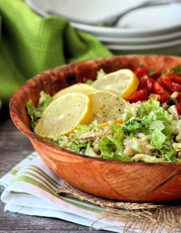 A deliciously healthy and light Mediterranean-inspired Tuna and Orzo Salad with organic roasted tomatoes, veggies, Feta Cheese, and a lemon vinaigrette dressing