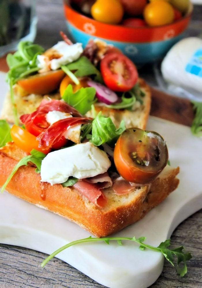 Treat your guests to a delicious flavorful lunchof Goat Cheese Tomatoes and Prosciutto on Ciabatta Bread in a snap! How can you go wrong with wonderful flavors likeGoat Cheese, Heirloom vine-ripened tomatoes, Prosciutto, pepperyArugula, fresh basil, garlic, and warm balsamic? It's a little slice of heaven if you ask me. go wrong with wonderful flavors likeGoat Cheese, Heirloom vine-ripened tomatoes, Prosciutto, pepperyArugula, fresh basil, garlic, and warm balsamic? Its a little slice of heaven if you ask me.