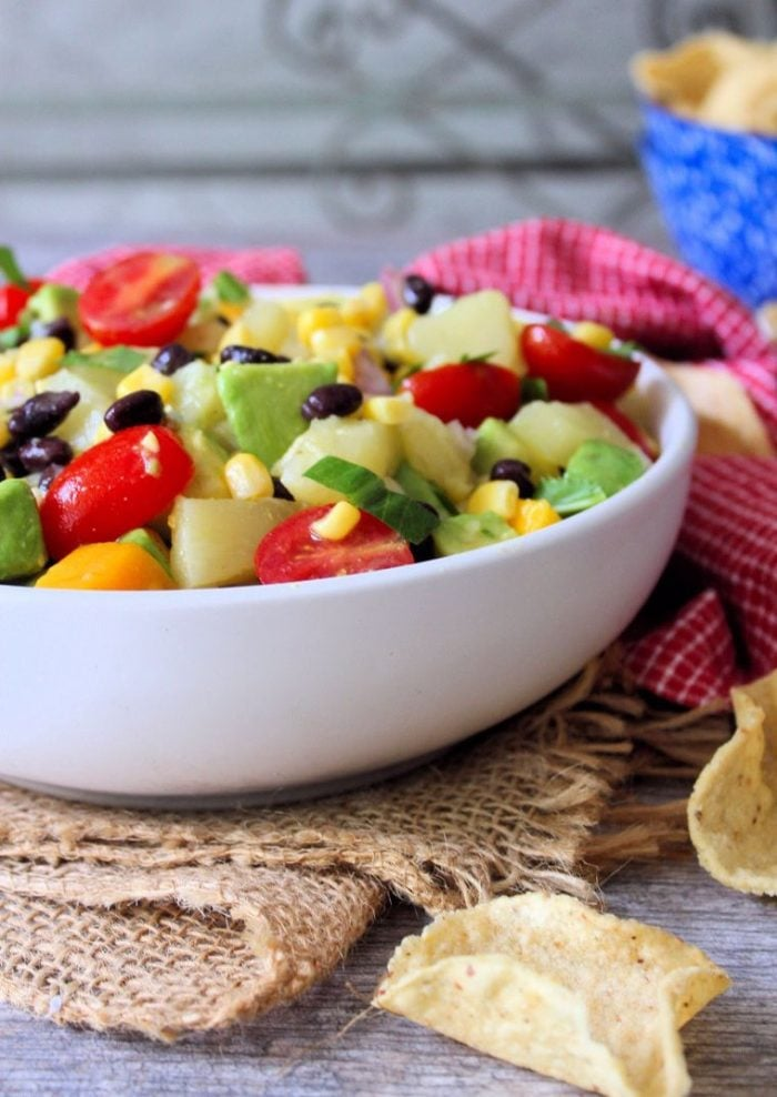 Make the perfect crowd pleaser in just a matter of minutes with this deliciously flavorful fresh-tasting Black Bean and Corn Salsa with Pineapple and Mango that your family and friends will enjoy on tortilla chips, tacos, salads, grilled chicken, fish, or even steak.
