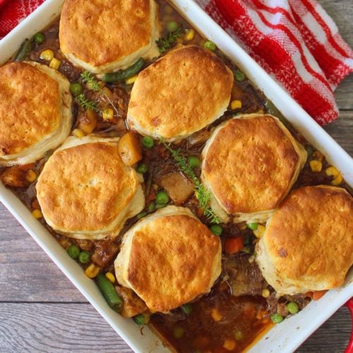 This classic stick-to-your-ribs Beef and Biscuits Casserole is the ideal flavorful meal for a weeknight dinner or busy weekend. Beef, onion, carrots, potatoes, peas, and green beans, topped with deliciously fluffy biscuits come together in a cozy harmony.
