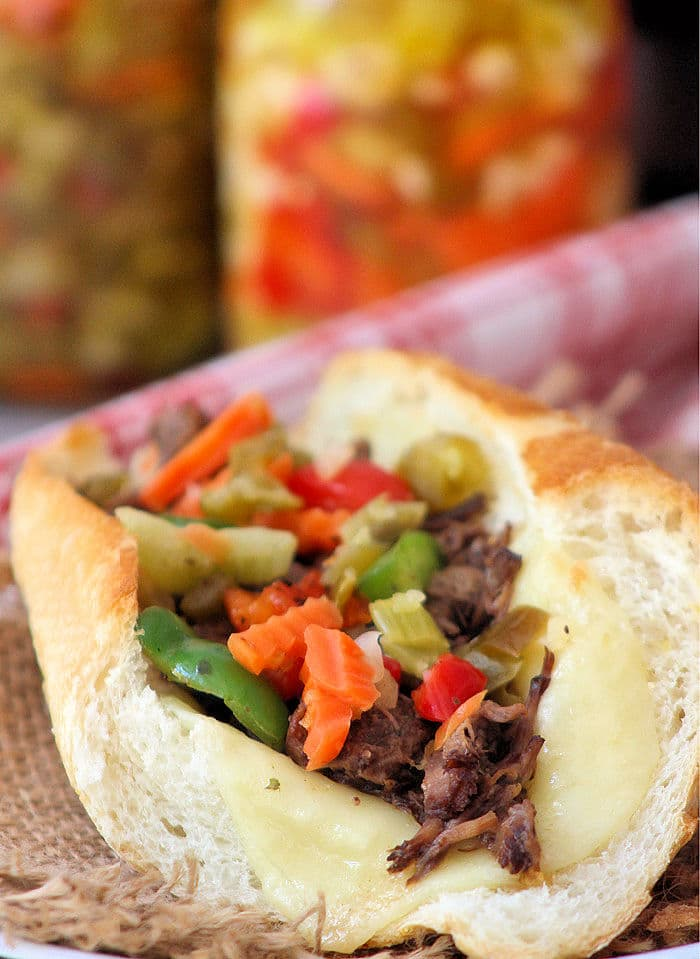 This classic Italian beef sandwich comprises of juicy shredded roast beef, fried sweet bell peppers, a spicy giardiniera, and provolone on a crusty bread roll.